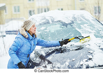 Woman cleaning car from snow