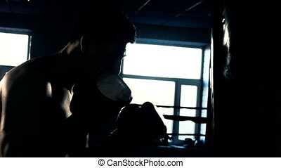 Young male sportsman athlete training in boxing gym. Boxer...