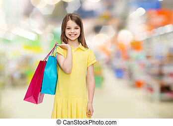 smiling girl with shopping bags over supermarket - sale,...