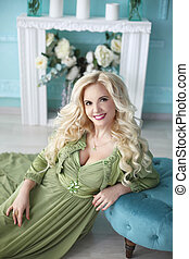 Beautiful smiling blond woman with long curly hair style wears in green dress posing on the floor over decor flowers blue wall, home interior.