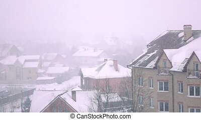 Snowstorm above sloped roofs of residential houses in winter...