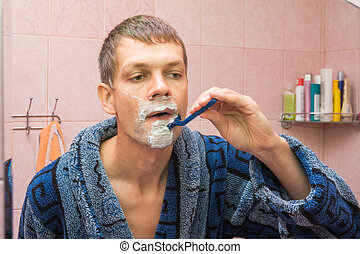 Young man shaving in front of mirro