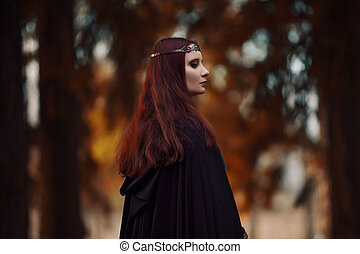 Young beautiful and mysterious woman in woods, in black...