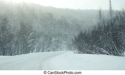 Car driving on snow beautiful road during snowfall in...