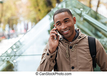 Cheerful young african man talking on phone in the street -...