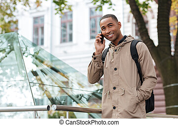 Cheerful young african man talking on his phone at street -...