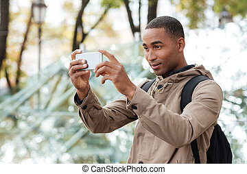 Young dark skinned man photographing outdoors with his...