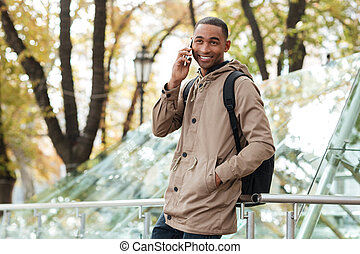 Young african man with backpack talking on phone at street -...