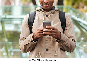 Cropped photo of cheerful dark skinned man using cellphone -...