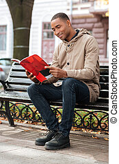 African happy man reading a book while sitting on bench -...
