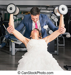 Bloom helping bride with weights in the gym
