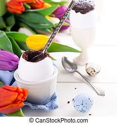 Easter egg filled with chocolate cake, tulips and colorful...