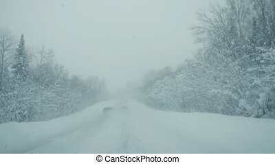 Car driving on snow road during strong snowfall in...