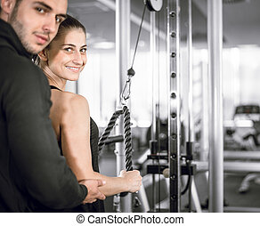 Personal fitness trainer with his client in gym. - Young...