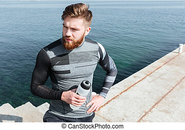 Male runner with water near the sea. on dock. man looking...