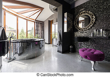 Posh bathroom with oval bath enclosed in small mirror tiles