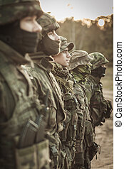 Heavily armed soldiers in a row - Heavily armed soldiers in...