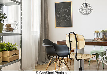 Light room with communal table, chairs, industrial lamp and...
