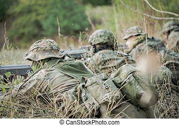 Camouflaged army soldiers with guns - Camouflaged army...