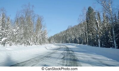 Winter landscape with road at forest and the blue sky in...