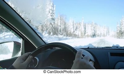 Man's hands of a driver on steering wheel on winter landscape outdoors in slow motion. 1920x1080