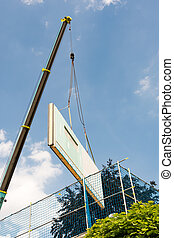 Assembling a prefabricated house - wall is hanging on a...