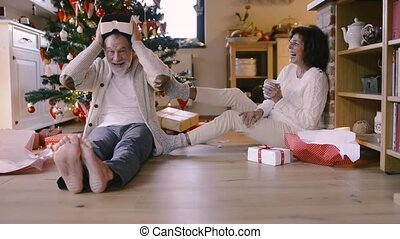 Senior couple in front of Christmas tree unpacking presents....