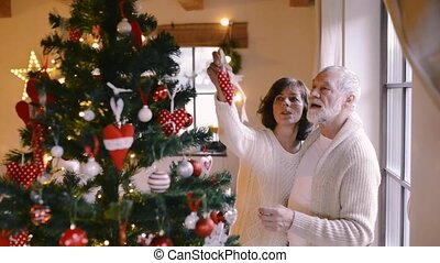 Senior couple at home decorating Christmas tree.