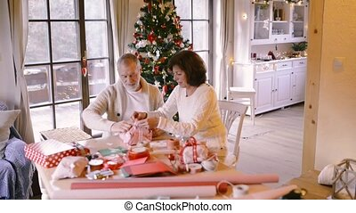 Senior couple in sweaters wrapping Christmas gifts together....