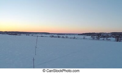 Aerial video of small power line pylons and distant houses...