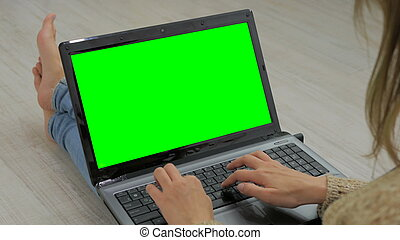 Woman using laptop with green screen. Woman's hands typing...