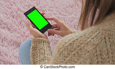 Woman looking at smartphone with green screen. Close up shot...