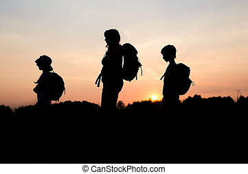 Silhouettes of mom hiking with her kids at sunset
