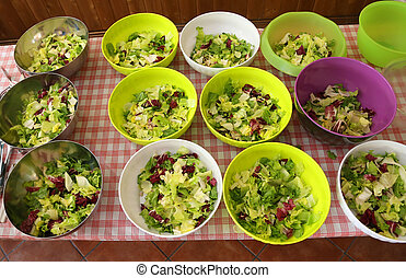 table with many bowls of lettuce and salad in the lunchroom...