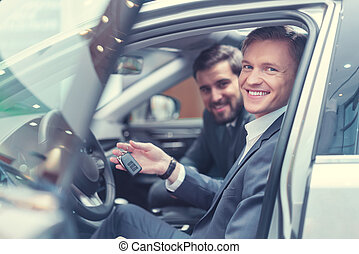 Dealership - Happy young businessmen in car