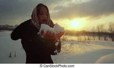 Winter portrait of a beautiful young woman blowing snowflakes and smiling in slowmotion during sunset. 1920x1080