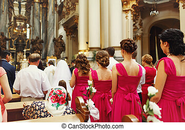 Bridesmaids in pink dresses pray during the ceremony in church