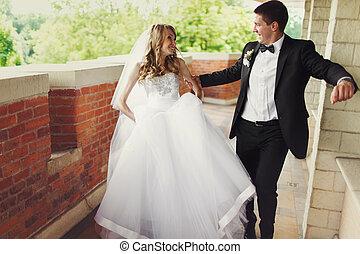 A wedding couple has fun while walking along the balcony