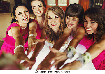 Bride and bridesmaids reach their hands out and smile