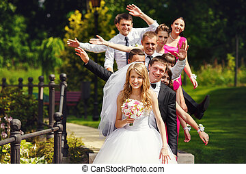Bridesmaids and groomsmen pose with open hands standing behind groom and bride