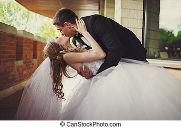 Bride touches groom's head tenderly while he bends her over...