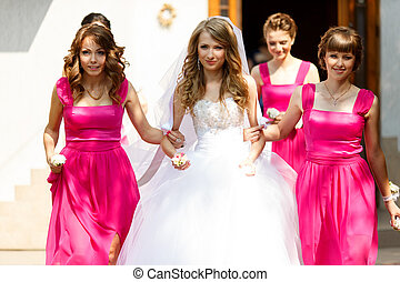 Bridesmaids in pink dresses hold bride's arms walking out of...