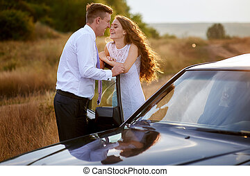 bride and groom kissing near car on wedding walk.