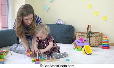Cute small girl put colorful wooden bricks into mother...