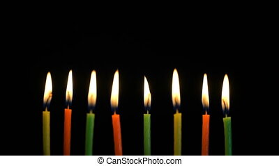 Footage colorful burning candles set on black background.
