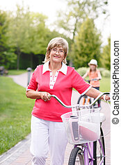 Active senior woman riding bike in a park