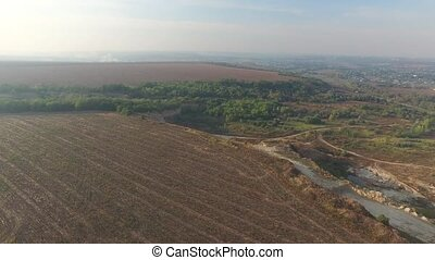Flying over the plowed field and sand pit in grove - Aerial...
