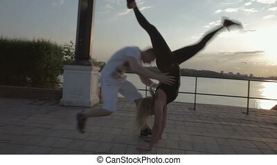 Girl and men dancing strip plastic at sunset stock footage...