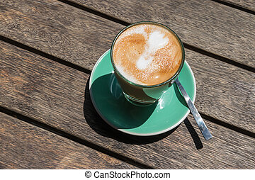 caffe latte on wooden table - closeup of caffe latte on...