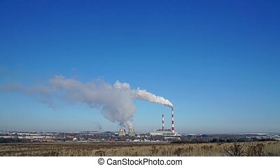 Thermal power plant or a factory with Smoking chimneys. Polluting smoke into the clear blue sky.